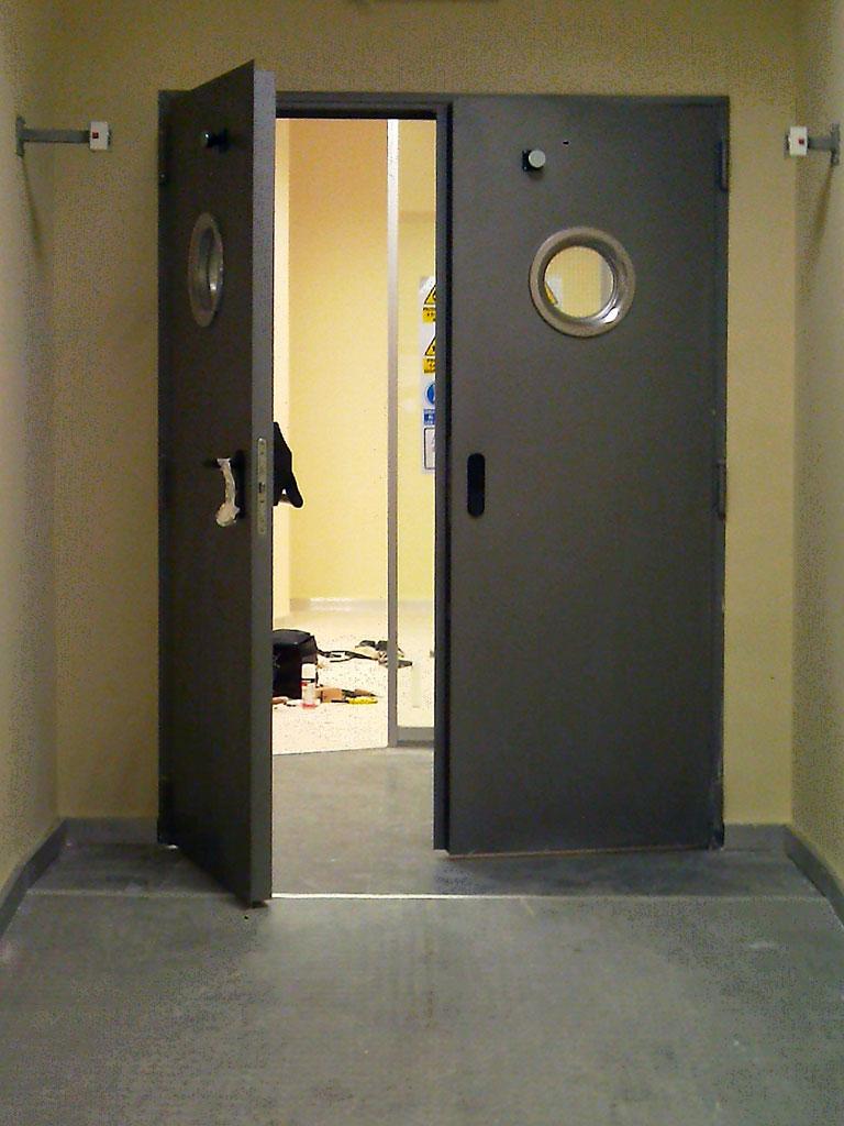 Puerta metálica de entrada a oficina, lacada en color corporativo.